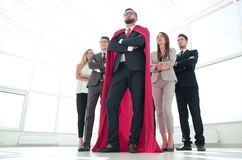 Leader in the red cloak and the business team standing together. Bottom view.the leader in the red cloak and the business team standing together.business concept stock images