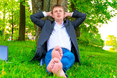 Leader relaxes sitting against a tree Royalty Free Stock Photography