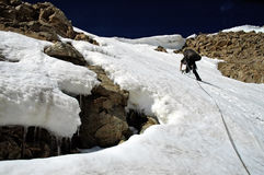 Leader on a rope. Brave rope leader storming snow wall with a cornice Royalty Free Stock Photo