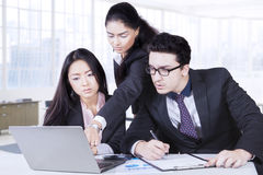 Leader showing a job on the laptop. Indian female leader team showing a job to her employees on the laptop at office royalty free stock photo