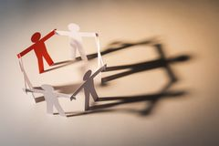 Leader of six cooperate in light. Closed joining of six paper figure on light background. in concept of business, cooperation and leadership stock image
