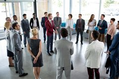 Leader standing in circle of his successful business team stock photo