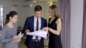 Leader stands and checks papers that are given by female employees in office. Man in a business suit studies charts and diagrams on documents in center of stock video footage