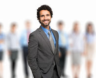 Leader stands with coworkers in background Stock Photography