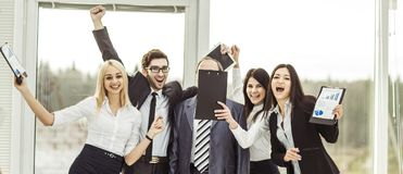 Boss and happy business team rejoice after signing a lucrative financial contract. Leader and successful business team cheering after signing a lucrative Stock Photos