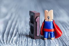 Leader superhero concept. Clothespin super hero and 1 one written with colored vintage letterpress. soft focus, copy Stock Images