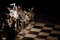 Leader of the troops. A chessboard with hand sculpted pieces and the King spot lit royalty free stock photo