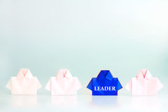 Leader word on One blue among white origami shirt paper , unique Stock Photography