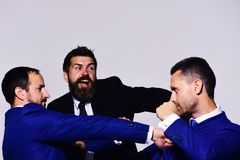 Leaders fight for business leadership. Coworkers decide upon best position. Rivalry and business confrontation concept. Businessmen with serious and excited stock photos