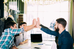 We are leaders on the market. Cheerful young people giving each other high-five with smile while sitting at the office table on bu stock image
