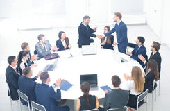Leaders of the two business teams shake hands at a business meet. Two business team with documents and laptops sitting at a round table and applaud their leaders Stock Photos