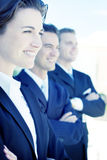 Leadership. One female two males wearing dark business suits in a row smiling Stock Image