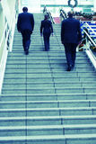 Leadership. Rear view of three people climbing stairs in business suits Stock Photography