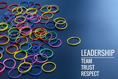Leadership business concept. yellow color rubber band lead other color with word Leadership, team, trust and respect royalty free stock image