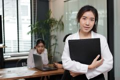 Leadership business woman concept. Cheerful young Asian businesswoman with ring binder standing against her colleague in office stock photos