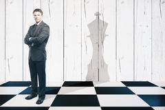 Leadership. Businessman with folded arms standing on chessboard with king piece shadow on textured wooden wall. Leadership concept royalty free stock photo