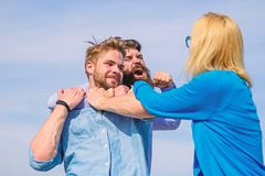 Leadership and competition concept. Man aggressive attacks lover his girlfriend. Men fighting for heart of lady. Woman. Tries stop violence, men fighting royalty free stock image