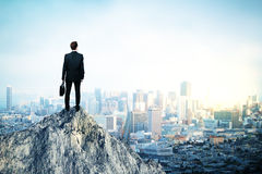 Leadership concept. Back view of young man in suit and with briefcase in hand standing on mountain top. City background with copy space. Leadership concept royalty free stock photography