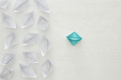 leadership concept, blue paper boat leading followers over white background Royalty Free Stock Image