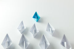 Leadership. Concept with blue paper ship leading among white Stock Image