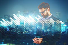 Leadership concept. Businessman using smartphone on abstract city background with business chart bars. Leadership concept. Double exposure Royalty Free Stock Image