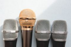 Leadership concept. group of microphones with golden one. freedom to speak up concept.  stock photos