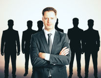Leadership concept. With handsome caucasian businessman in front of businesspeople silhouettes Stock Photography