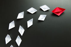 Leadership concept illustrated with paper ships. Leadership concept with red ship leading among the white Stock Photography