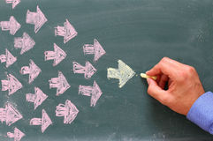 Leadership Concept image, male hand drawing arrows. Over chalkboard Stock Photo