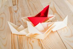 Pile of origami paper boats with a red ship on the top on wooden background Royalty Free Stock Images