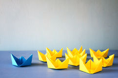 Leadership concept with paper boats on wooden background. Leadership concept with paper boats on blue wooden background. One leader ship leads other ships Stock Image