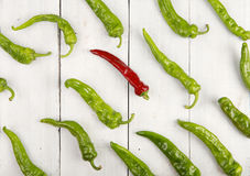 Leadership concept - red hot chili pepper leading the group of green ones Stock Photos
