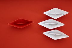 Leadership concept with red paper ship. Leading among white on red background with copy space. Business leadership concept. Minimal design Stock Photography