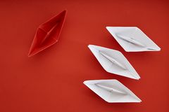 Leadership concept with red paper ship. Leading among white on red background with copy space. Business leadership concept. Minimal design Stock Photos
