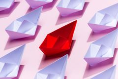 Leadership concept. Red paper ship leading among white Stock Photos