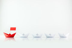 Leadership. Concept with red paper ship leading among white Royalty Free Stock Photography
