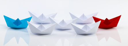 Leadership concept with red paper ship leading among white.  Royalty Free Stock Image