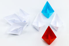Leadership concept with red paper ship leading among white.  Royalty Free Stock Photo