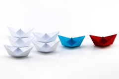 Leadership concept with red paper ship leading among white.  Royalty Free Stock Photos