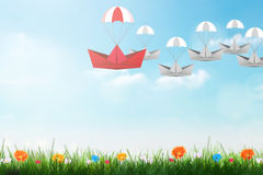 Leadership concept with red paper ship with parachute leading among white, Unique and different concept. Stock Image