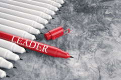 Leadership concept with red pen. Among white pens stock photography