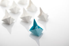 Leadership concept using blue paper ship. Among white Royalty Free Stock Images