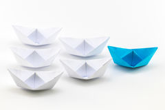 Leadership concept using blue paper ship among white.  Stock Images