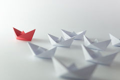 Leadership. Concept using red paper ship among white stock photography