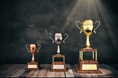 Leadership concept. Wooden stage with golden, silver and bronze winnner& x27;s cups on concrete background. Leadership concept. 3D Rendering Royalty Free Stock Images