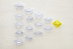 leadership concept, yellow paper boat leading followers over white background Royalty Free Stock Photography