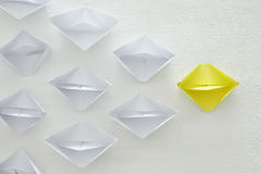 leadership concept, yellow paper boat leading followers over white background Stock Photography