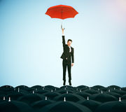Leadership concept. Young businessman with red umbrella flying above black umbrellas on blue background. Leadership concept. 3D Rendering Royalty Free Stock Photography