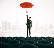 Leadership concept. Young businessman with red umbrella flying above black umbrellas on city background. Leadership concept. 3D Rendering royalty free illustration