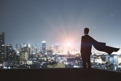 Leadership and confidence concept. Young backlit super hero businessman on rooftop with night city view. Leadership and confidence concept royalty free stock photos